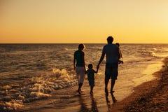Силуэты семьи на пляже на заходе солнца стоковое фото rf