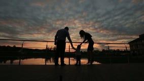 Силуэты счастливой семьи идя совместно на заход солнца