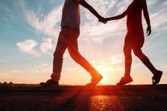 Силуэты счастливых пар бежать вниз на заходе солнца, совершенной предпосылке влюбленности стоковое фото rf