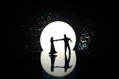 Силуэты танцев пар игрушки под луной на ноче Диаграммы человека и женщины в танцах влюбленности на лунном свете Стоковые Фото