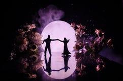 Силуэты танцев пар игрушки под луной на ноче Диаграммы человека и женщины в танцах влюбленности на лунном свете Стоковые Фотографии RF