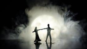 Силуэты танцев пар игрушки под луной на ноче Диаграммы человека и женщины в танцах влюбленности на лунном свете Стоковое Фото