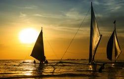 Силуэты шлюпок на красивом заходе солнца на пляже Стоковая Фотография
