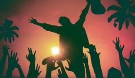 Силуэты людей в музыкальном фестивале концепцией пляжа стоковое изображение