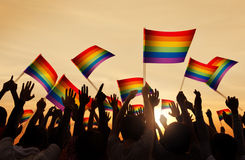 Силуэты людей держа флаг символа гей-парада Стоковая Фотография RF