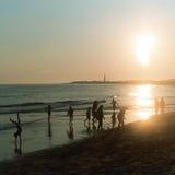 Силуэты людей наслаждаясь пляжем как солнце устанавливают на стоковое фото rf