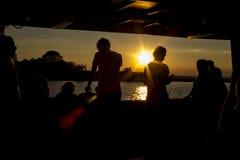 Силуэты людей на заходе солнца Отключение вечера к острову стоковая фотография