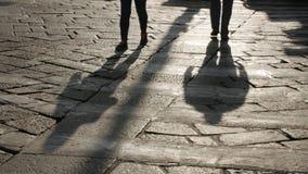 Силуэты людей на мостоваой булыжника стоковая фотография