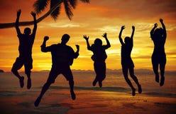 Силуэты людей скача морем Стоковые Фотографии RF