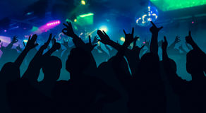 Силуэты людей танцев перед ярким этапом освещают Стоковое Фото