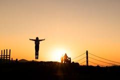 Силуэты hikers наслаждаясь заходом солнца Стоковые Изображения