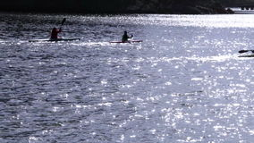 Силуэты kayakers группы на реке