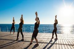 Силуэты sportive девушек танцуя zumba около моря на восходе солнца Стоковое фото RF