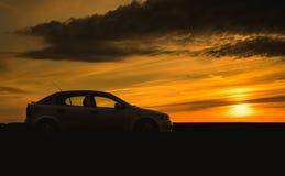 Силуэт автомобиля в заходе солнца Стоковые Фотографии RF
