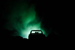 силуэт автомобиля с парами внутрь на темной предпосылке с светами и дымом романтичное место человек влюбленности поцелуя принципи Стоковые Фото