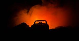 силуэт автомобиля с парами внутрь на темной предпосылке с светами и дымом романтичное место человек влюбленности поцелуя принципи Стоковые Изображения RF