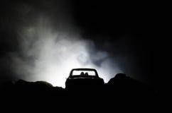 силуэт автомобиля с парами внутрь на темной предпосылке с светами и дымом романтичное место человек влюбленности поцелуя принципи Стоковые Фотографии RF