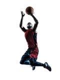 Силуэт африканского баскетболиста человека скача бросая Стоковые Фото