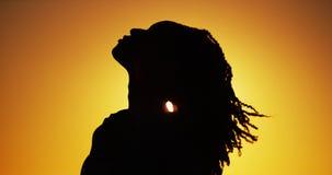 Силуэт африканской женщины стоя на заходе солнца Стоковая Фотография RF