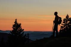 Силуэт альпиниста на заходе солнца Стоковые Фотографии RF