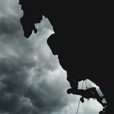 Силуэт альпиниста на скале во время дождевого облако Стоковые Фотографии RF