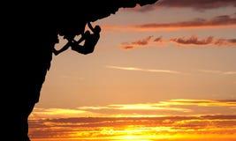 Силуэт альпиниста на стороне утеса Стоковые Изображения RF