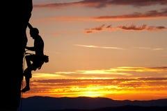 Силуэт альпиниста на стороне утеса Стоковая Фотография RF