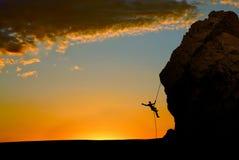 Силуэт альпиниста утеса на заходе солнца Стоковое Изображение RF
