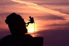 Силуэт альпиниста утеса человека над ярким заходом солнца Стоковое Фото