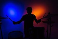 Силуэт барабанщика человека сидя и играя барабанит с ручками Стоковое Фото