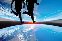 Силуэт бега спортсменов женщин, фона планеты Стоковая Фотография