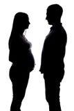 Силуэт беременной женщины и молодого человека Стоковое Фото