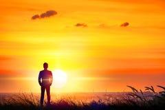 Силуэт бизнесмена стоя на холме захода солнца стоковое фото rf