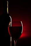 Силуэт бутылки и стекла вина над темнотой - красным цветом Стоковые Фотографии RF