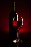 Силуэт бутылки и стекла вина над темнотой - красным цветом Стоковые Изображения RF