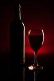 Силуэт бутылки и стекла вина над темнотой - красным цветом Стоковое Изображение