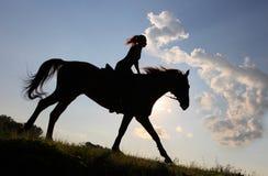 Силуэт верховой лошади пастушкы через прерию сумрака Стоковая Фотография RF