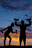 Силуэт весов человека и женщины поднимаясь в заходе солнца Стоковые Фото
