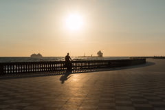 Силуэт велосипеда катания женщины на Livorno& x27; s Mascagni Terrac Стоковое фото RF