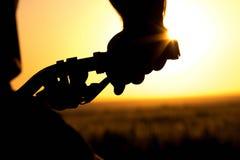 Силуэт велосипеда катит внутри поле Стоковые Фото