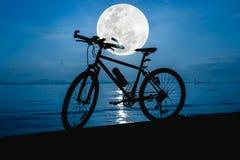 Силуэт велосипеда на пляже против красивого полнолуния i Стоковые Фото
