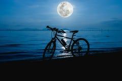 Силуэт велосипеда на пляже против красивого полнолуния i Стоковая Фотография