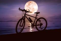 Силуэт велосипеда на пляже против красивого полнолуния i Стоковое фото RF