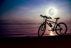 Силуэт велосипеда на пляже против красивого полнолуния i Стоковые Фотографии RF