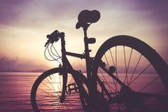 Силуэт велосипеда на пляже против красочного захода солнца в th Стоковая Фотография
