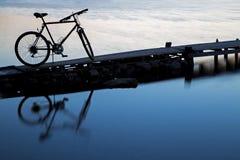 Силуэт велосипеда отражая на воде Стоковые Фотографии RF