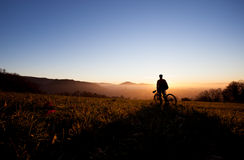 Силуэт велосипедиста в заходе солнца Стоковое Изображение RF