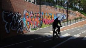 Силуэт велосипедиста вдоль дороги с граффити стоковое изображение