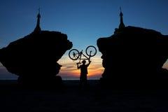 Силуэт велосипедиста между 2 stupas на предпосылке  Стоковая Фотография