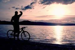 Силуэт велосипедиста молодого человека на голубом небе и заходе солнца над пляжем Велосипедист в конце сезона на озере Стоковое Изображение RF